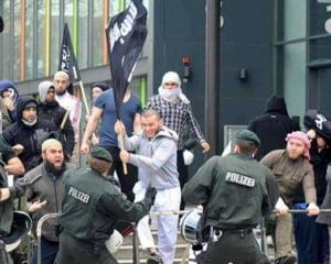 Ati vazut fotografia cu refugiatul care se lupta cu politia din Germania si flutura un steag ISIL? Este un fals (Video)